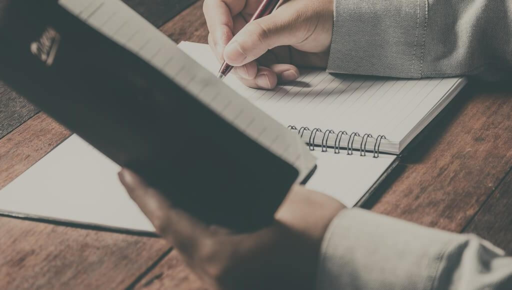 The Ultimate Start-up Checklist image - man's arms writing in a notebook on a wooden desk