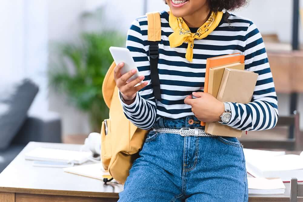 Woman sitting on desk holding books and looking at phone