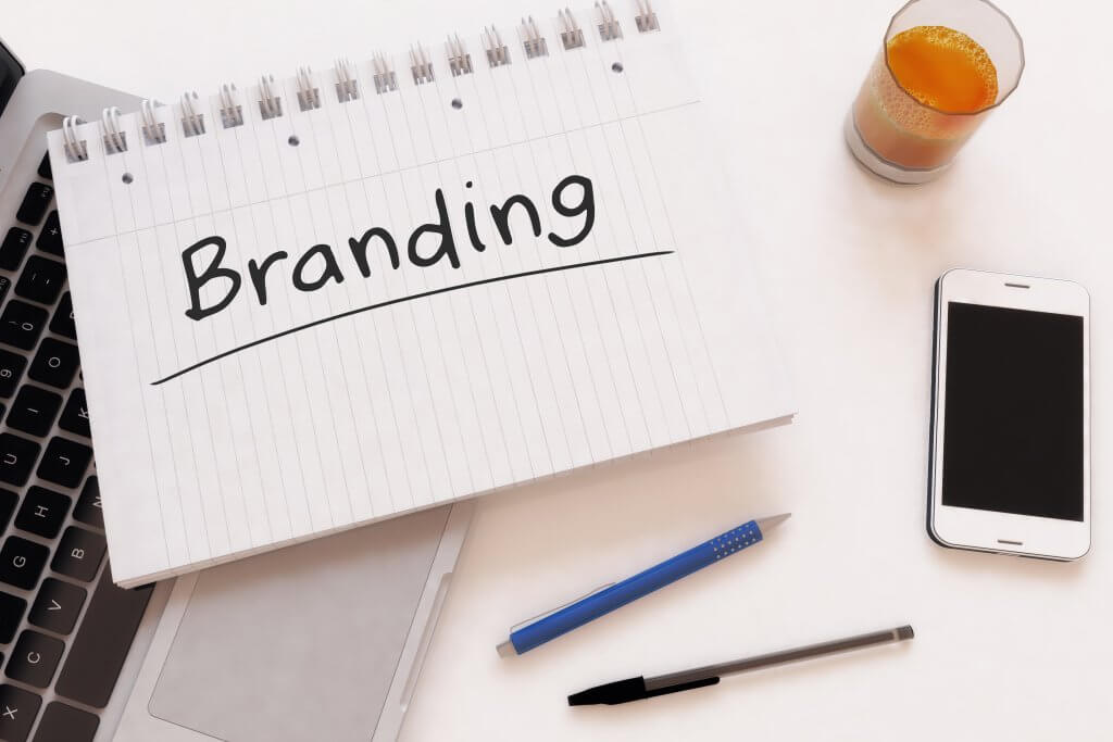 Naming Your Brand - Image - Notepad with branding written on it, plus a glass of juice, a phone and pens on a desk