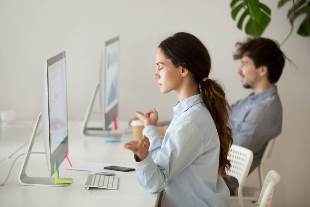 Image - female office worker meditating at her desk in front of computer, hands pressed together